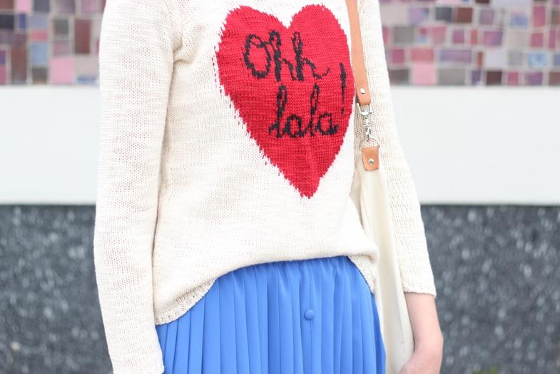 Dziewczęcy sweter z zabawnym napisem i kształtem serca połączony jest z plisowaną spódnicą.